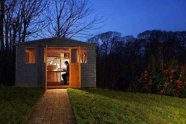 Abri de jardin en bois qui abrite une pièce supplémentaire transformée en bureau