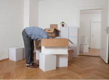Homme la tête dans les cartons pendant déménagement