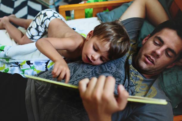 Papa qui lit une histoire à son fils avant de le mettre au lit