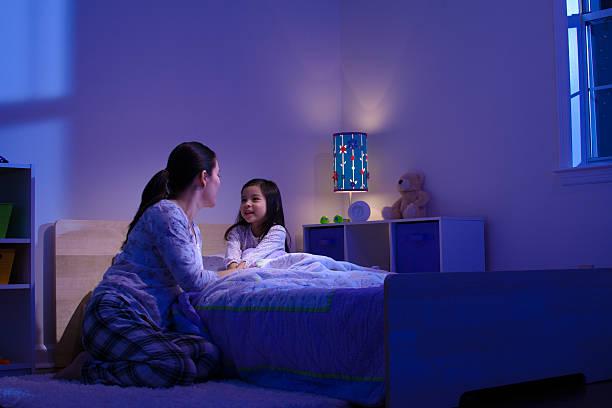 Maman pendant le rituel du coucher avec sa fille pour éviter les troubles du sommeil