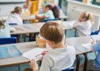 Salle de classe primaire avec élèves qui travaillent à leur bureau
