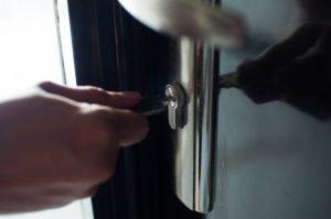 Homme en train d'ouvrir avec une clé la porte de son appartement