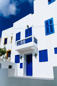 Maison style méditerranéen blanche et bleue, avec volets et portes peints en bleu vif