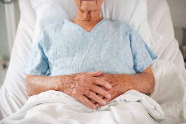 Personne âgée alitée dans un lit d'hôpital