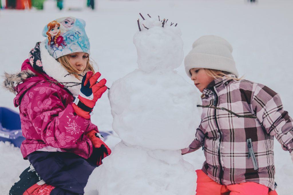 deux enfants habillés chaudement qui font un bonhomme de neige