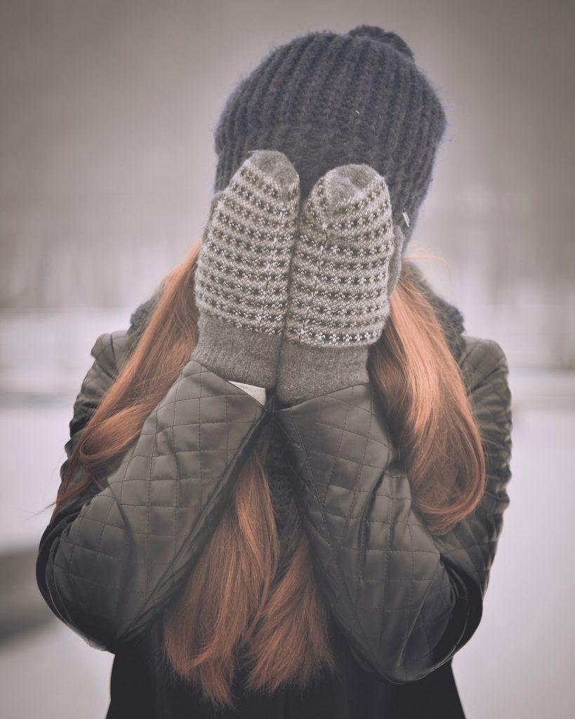 femme qui se cache le visage avec les mains portant des moufles et un bonnet
