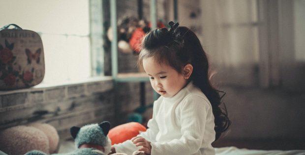 petite fille assise sur un lit qui joue avec ses doudous