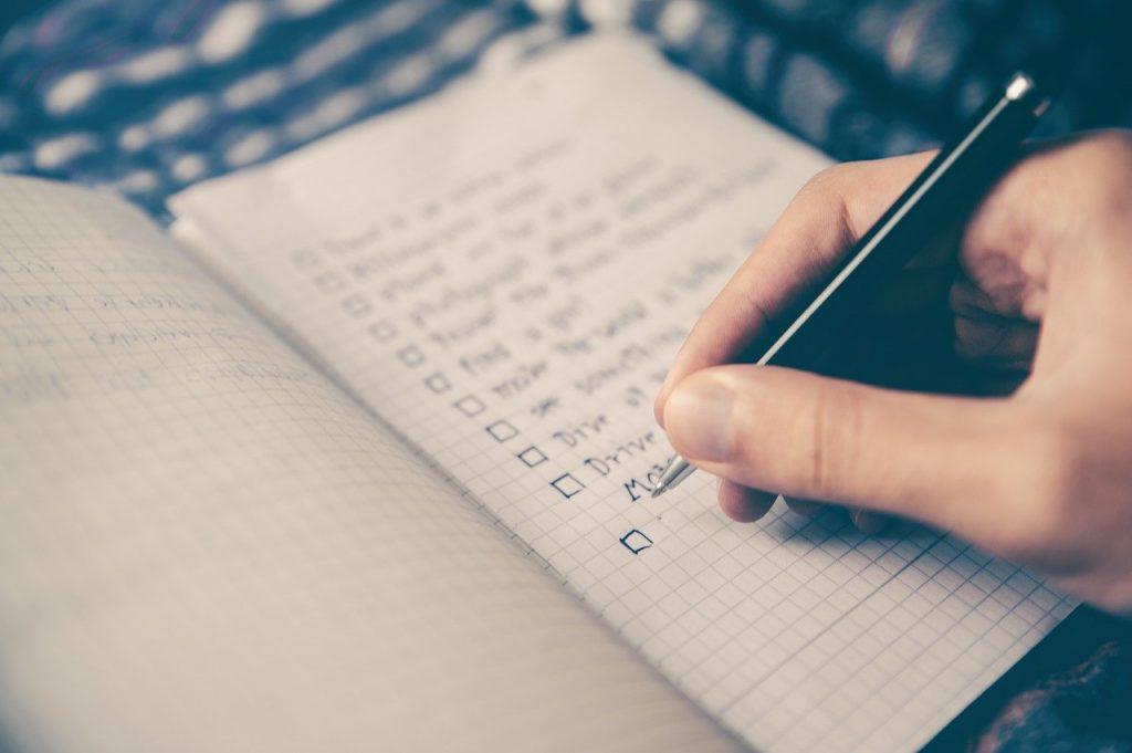 personne qui fait une liste dans un cahier